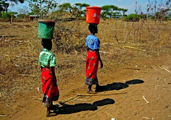 Villagers balance full water buckets on their heads, returning from their morning hike to a local spring.