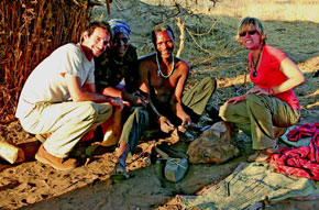 Randy, Mama Jeni, blacksmith Tumanne and Jennifer pose while two bracelets (on small rock) are being prepared for inscription with traditional tribal symbols.