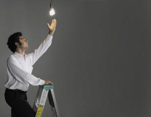 Businessman changing light bulb, studio shot