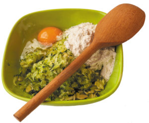 A bowl with flour, egg and grated zucchini for cooking pancakes