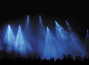 Konzert- oder Festivalpublikum als Silhouette vor blauem Licht - Hunderte von Fans feiern mit erhobenen Haenden eine Band