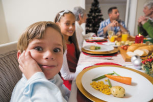 Portrait of little boy with a funny face at christmas dinner at home in the living room