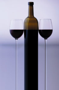 Stretched bottle and two glass goblets with red grape wine standing close to each other in studio isolated on white and grey backgroung, vertical picture