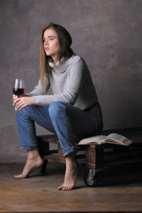 Model in sweater and jeans holding wineglass, girl with wineglass, high fashion look, sitting girl, beautiful girl, blonde girl, isolated, model in studio, girl wearing jeans and sweater, long hair, gray background